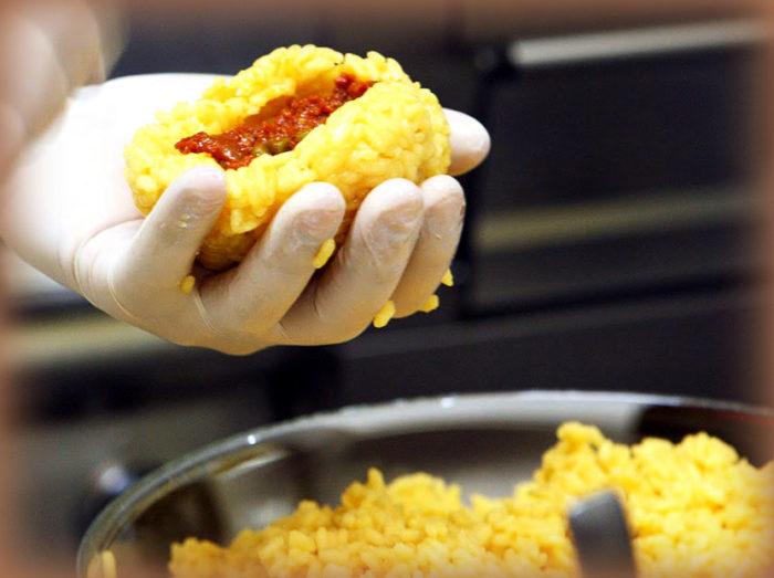 preparazione arancino siciliano al ragù