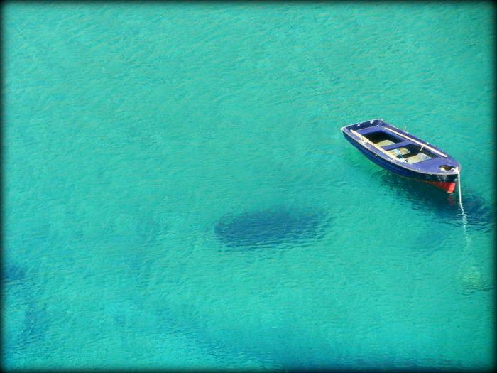 L'ombra di una barchetta sul fondale di un mare azzurro... Sicilia e niente altro...